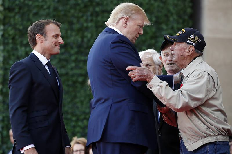 President Donald Trump and French President Emmanuel Macron, talk to a World War II veteran during a ceremony to commemorate the 75th anniversary of D-Day at the American Normandy cemetery