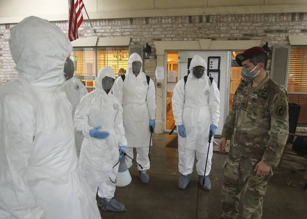Army National Guard Spc. Joel Mendoza, a chemical, biological, radiological, and nuclear specialist with the 1st Battalion (Airborne) of the 143rd Infantry Regiment, advises members of Joint Task Force 176 on proper wear of personal protective equipment in preparation for disinfecting the West Oaks Nursing and Rehabilitation Center in Austin, Texas, May 12, 2020.