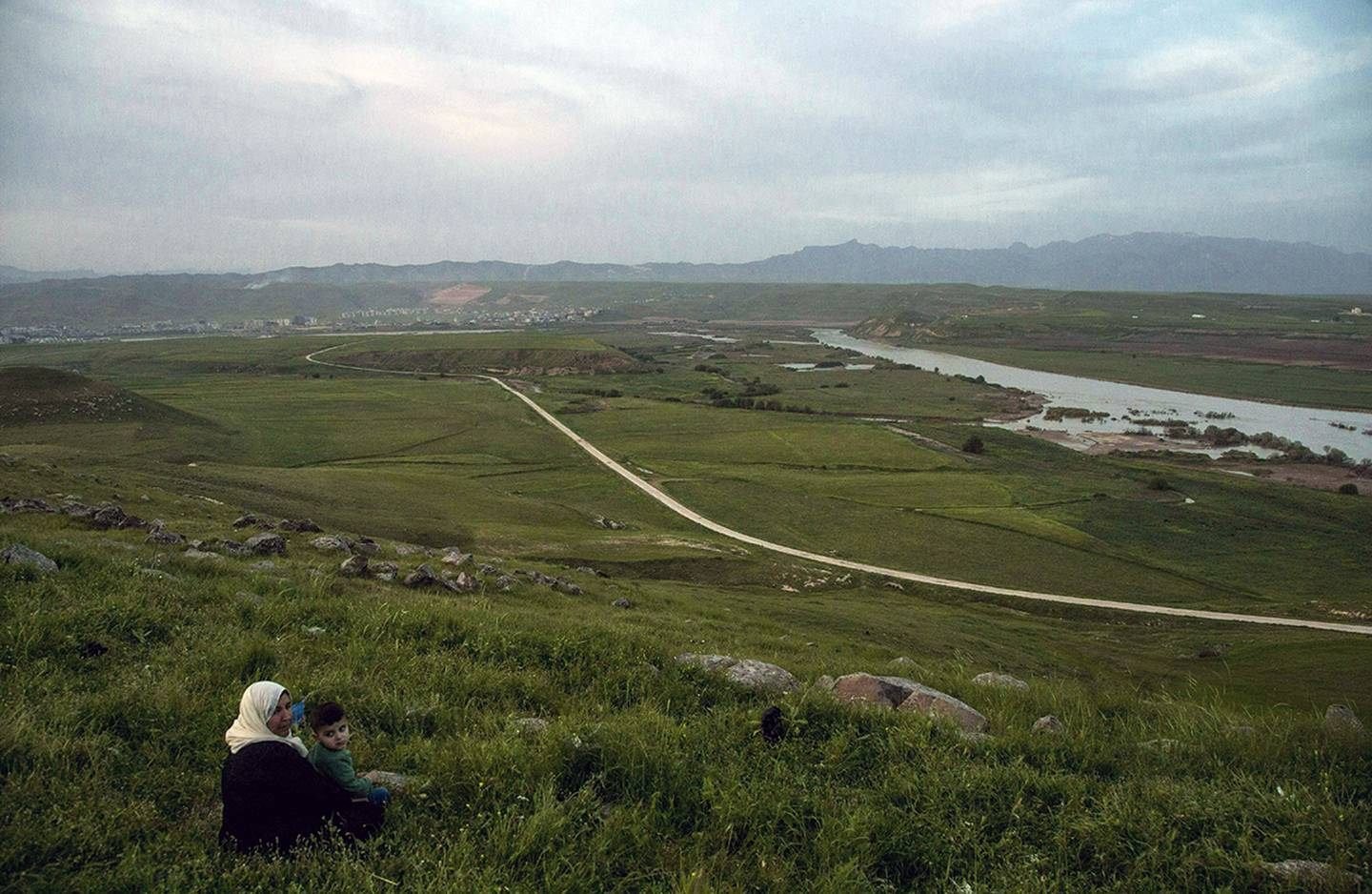 In this file photo dated May 1, 2019, a woman and child sit on a hill overlooking the Euphrates River as families picnic on May Day, in Derik, Syria.