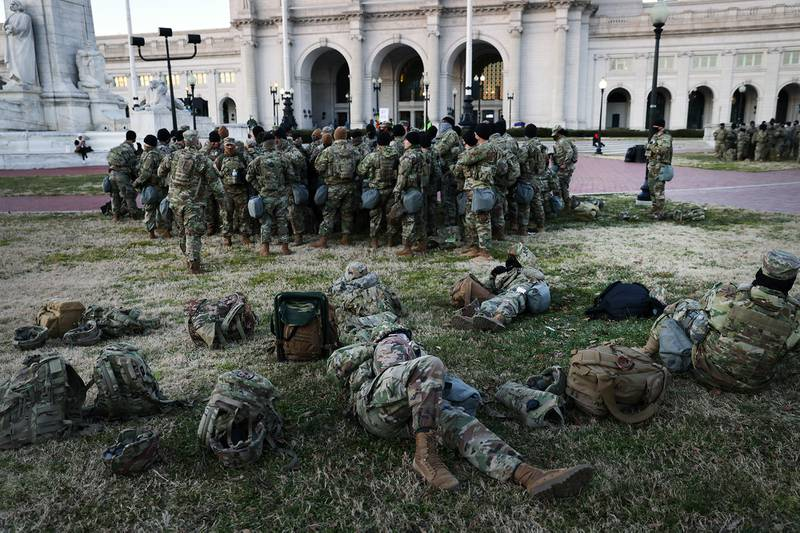 Members of the National Guard wait to depart Union Station as the city remains under tight security during the presidential inauguration on Jan. 20, 2021, in Washington.