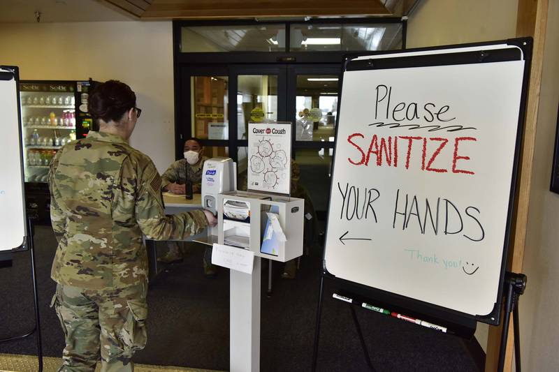 A 354th Medical Group Airman sanitizes her hands before entering the clinic