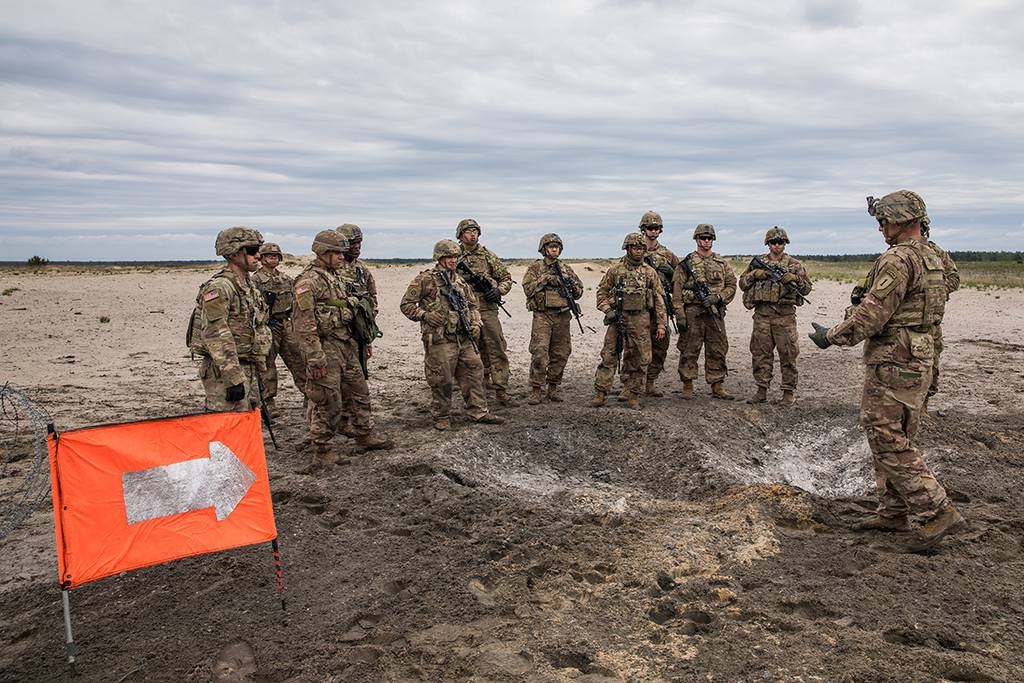 Soldiers conduct an after action review at the detonation site of a bangalore torpedo explosives during a day of breach training on a range near Camp Trzebień, Poland, May 23, 2019.