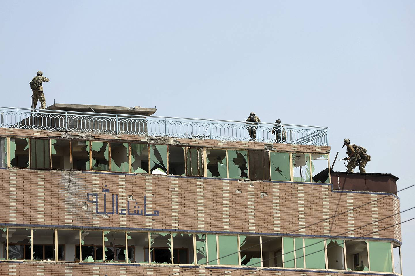 Afghan security personnel take position on the top of a building where insurgents were hiding, in the city of Jalalabad, east of Kabul, Afghanistan, Monday, Aug. 3, 2020.