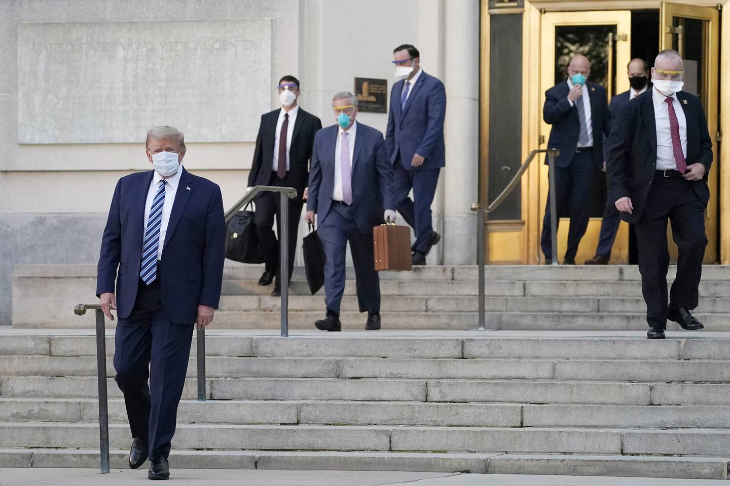 President Donald Trump, left, walks out of Walter Reed National Military Medical Center to return to the White House after receiving treatments for COVID-19, Monday, Oct. 5, 2020, in Bethesda, Md.