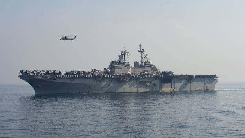 A SH-60 Sea Hawk flies over the amphibious assault ship USS Boxer (LHD 4) during a vertical replenishment-at-sea on July 19, 2019, in the Arabian Gulf.