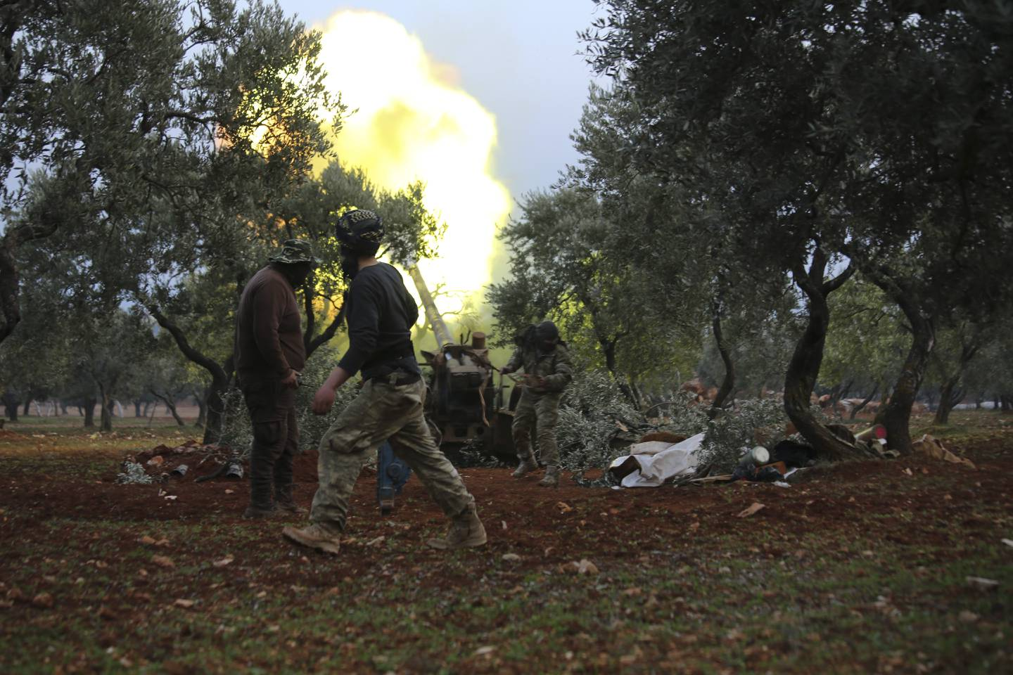 Syrian rebel fighters fire a howitzer