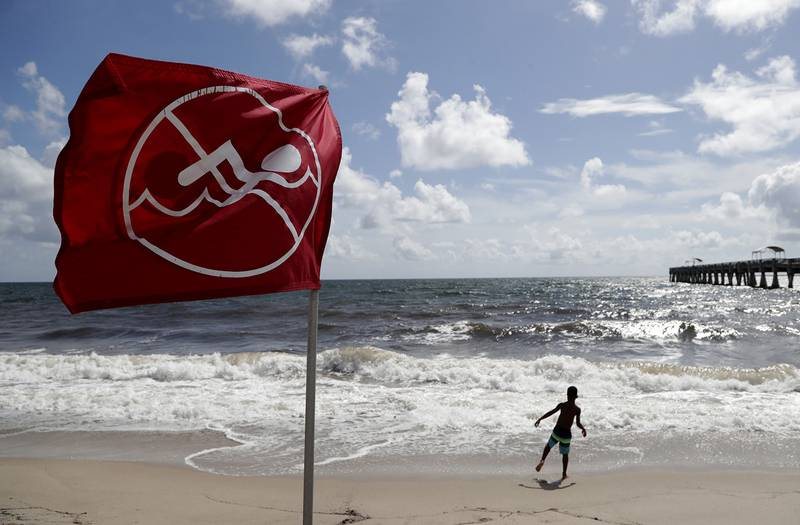 A boy plays on the beach as a No Swimming flag flies, Saturday, Aug. 31, 2019, in Lake Worth, Fla.