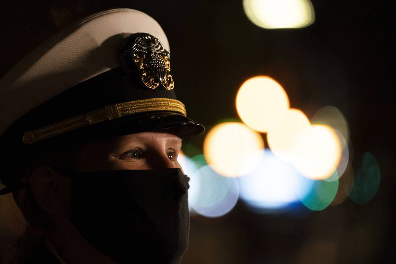A Navy officer joins in a wreath-laying ceremony at the Eternal Light Flagstaff in Madison Square Park, Wednesday, Nov. 11, 2020, in New York.