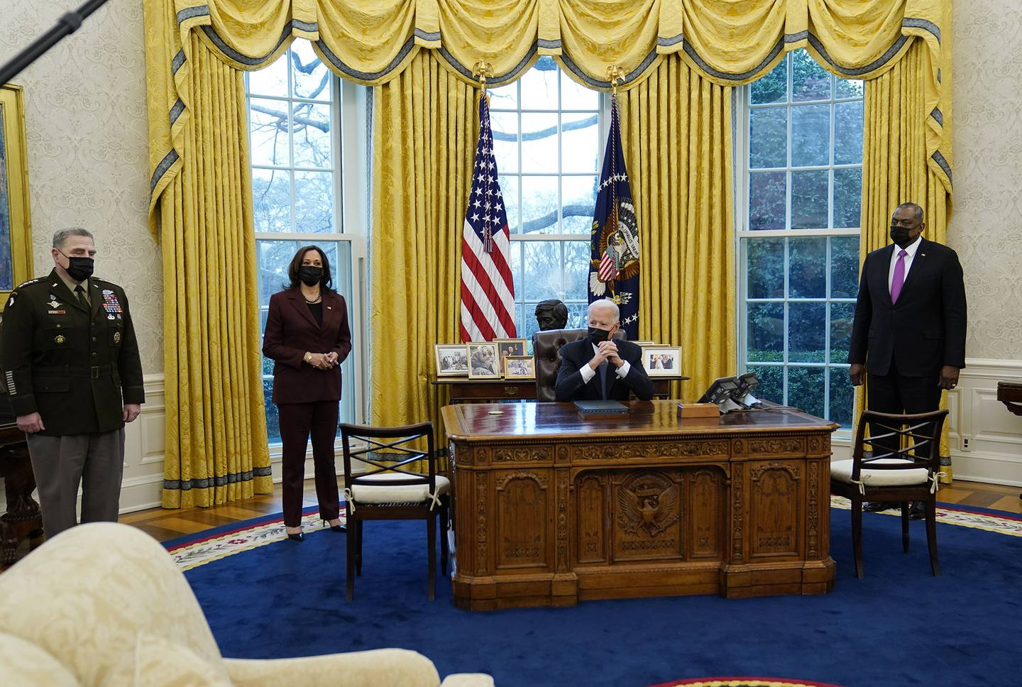 President Joe Biden meets with Secretary of Defense Lloyd Austin, right, Vice President Kamala Harris, and Gen. Mark Milley, chairman of the Joint Chiefs of Staff, left, in the Oval Office of the White House, Monday, Jan. 25, 2021, in Washington.