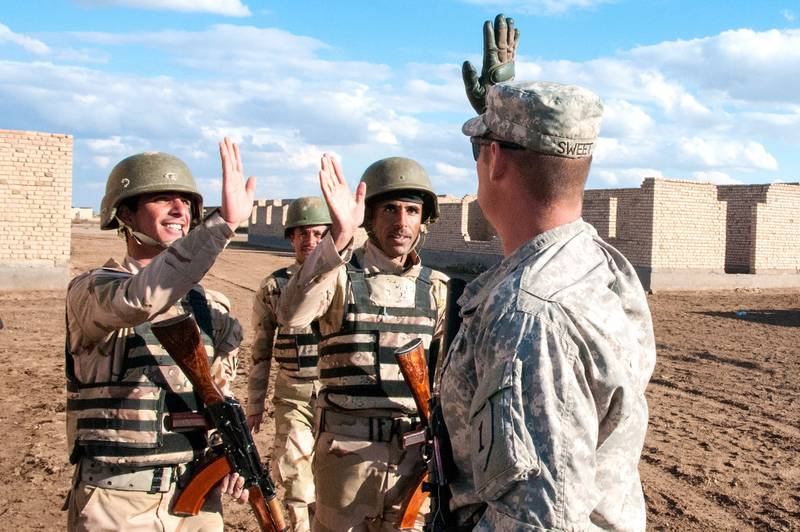 """A U.S. Army infantry trainer offers """"high fives"""" to two Iraqi Army trainees at the conclusion of the day's infantry squad tactical training lanes Jan. 8, 2015, at Camp Taji, Iraq."""
