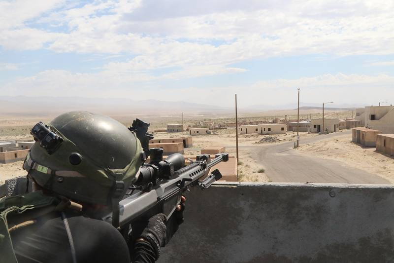 A soldier surveys the battlefield with a simulated BarrettM107 .50 caliber sniper rifle on July 12, 2019, in the city of Razish at the National Training Center at Fort Irwin, Calif.