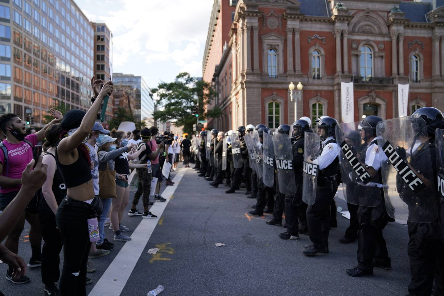 Demonstrators vent to police in riot gear as they protest the death of George Floyd, Saturday, May 30, 2020, near the White House in Washington. Floyd died after being restrained by Minneapolis police officers.