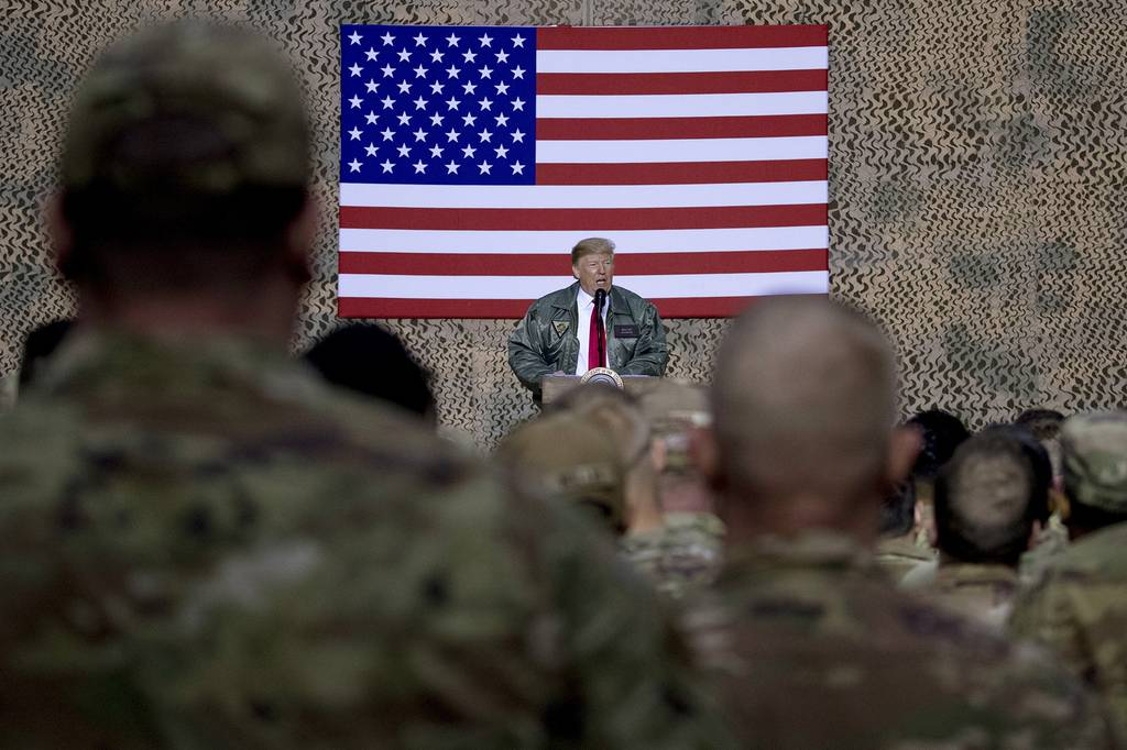 In this Dec. 26, 2018, file photo, President Donald Trump speaks to members of the military at a hangar rally at Al Asad Air Base, Iraq.