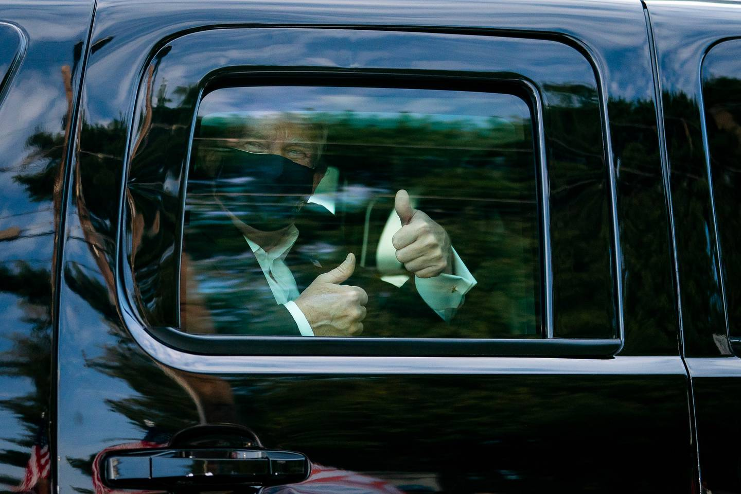 President Donald Trump greets supporters during a drive by outside of Walter Reed National Military Medical Center on Oct. 4, 2020, in Bethesda, Md.