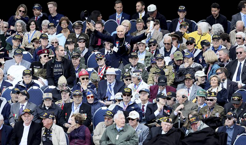 U.S. World War II veteran Jacques Michienzi, center, stands up among other veterans during a ceremony to mark the 75th anniversary of D-Day at the Normandy American Cemetery
