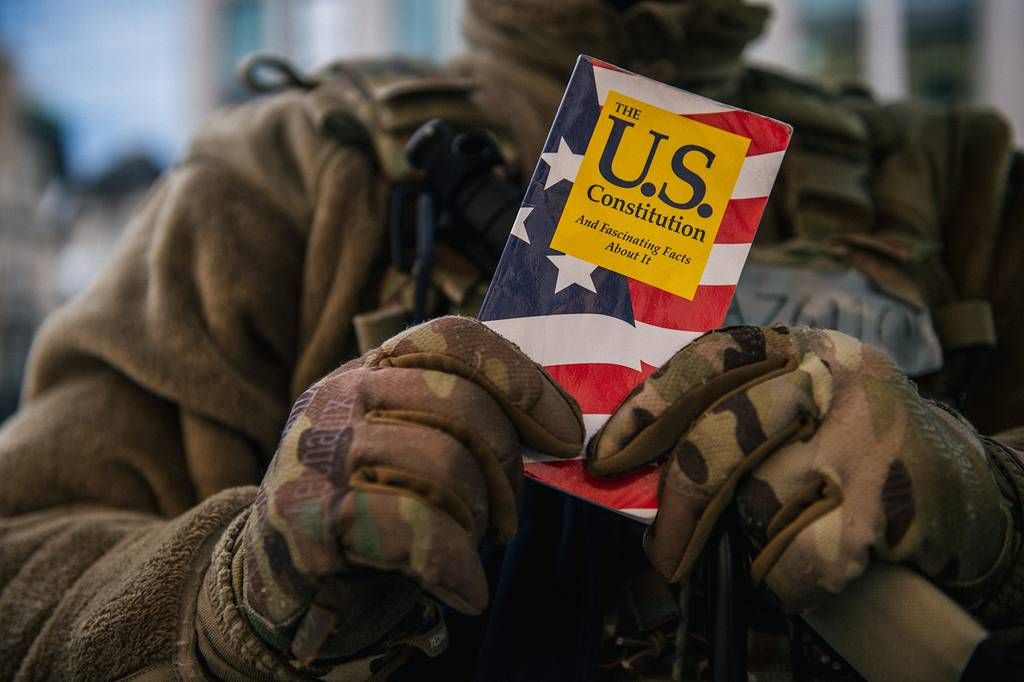 National Guard Master Sgt. George Roachs holds up a pamphlet of the U.S. Constitution on Jan. 17, 2021, in Washington. (