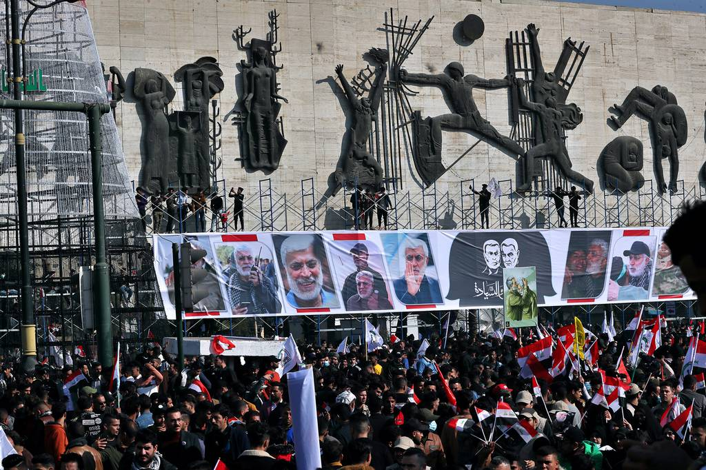 Supporters of the Popular Mobilization Forces hold a posters of Abu Mahdi al-Muhandis, deputy commander of the Popular Mobilization Forces, front, and Gen. Qassem Soleimani, head of Iran's Quds force during a protest, in Tahrir Square, Iraq, Sunday, Jan. 3, 2021.