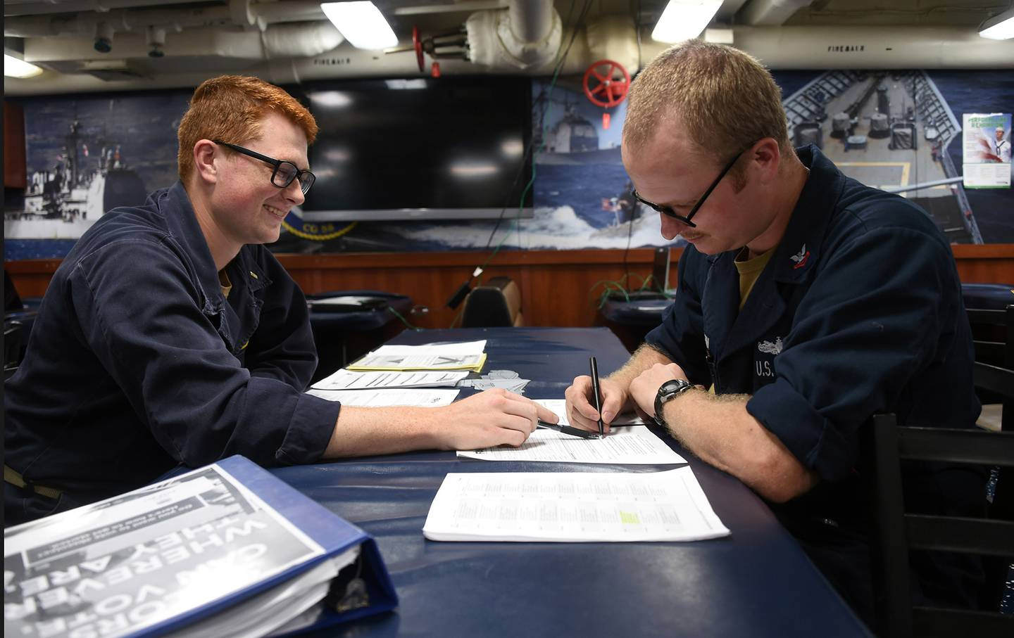 Unit Voting Assistance Officer Ensign Samuel Straub, left, assists Fire Controlman 2nd Class William Vaughn on absentee voting paperwork aboard the mess decks of the Ticonderoga-class guided-missile cruiser USS Philippine Sea (CG 58), Aug. 29, 2020.