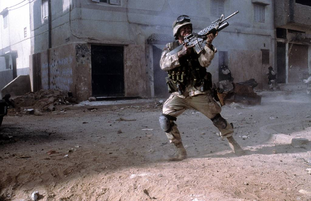 """A military man in combat in a scene from the 2001 film """"Black Hawk Down."""""""