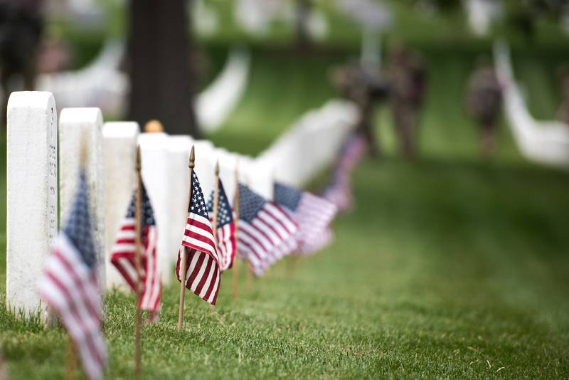 Soldiers with the 3d U.S. Infantry Regiment (The Old Guard) place flags at headstones in Arlington National Cemetery, Arlington, Va., during flags-In, May 23, 2019.