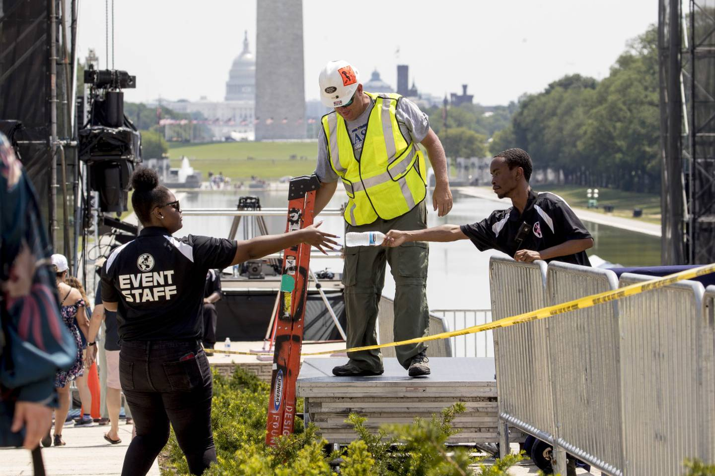 """The Capitol Dome, the Washington Monument and the Reflecting Pool are visible as workers set up for President Donald Trump's """"Salute to America"""" event honoring service branches on Independence Day at the Lincoln Memorial, Tuesday, July 2, 2019, in Washington."""