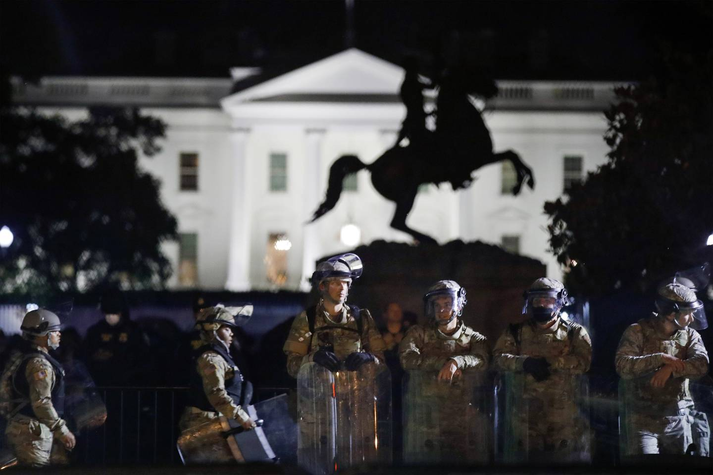 A line of DC National Guard members stand in Lafayette Park as demonstrators gather to protest the death of George Floyd, Tuesday, June 2, 2020, near the White House in Washington