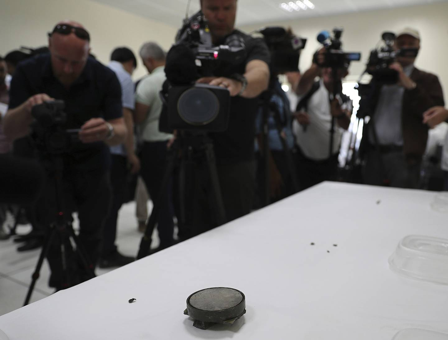 Journalists take pictures of a magnet the U.S. Navy says came from a limpet mine that didn't explode on a Japanese-owned oil tanker at a 5th Fleet base