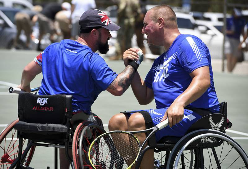 From left: Cpl. John Willans, Team United Kingdom, and Staff Sgt. Brian Biviano celebrate after they won their final match of wheelchair tennis