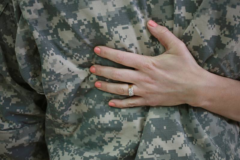 WO1 Anthony Woodmansee of the U.S. Army's 101st Airborne Division is embraced by his wife Emily Woodmansee during a homecoming ceremony at Campbell Army Airfield on March 21, 2015, in Fort Campbell, Ky.