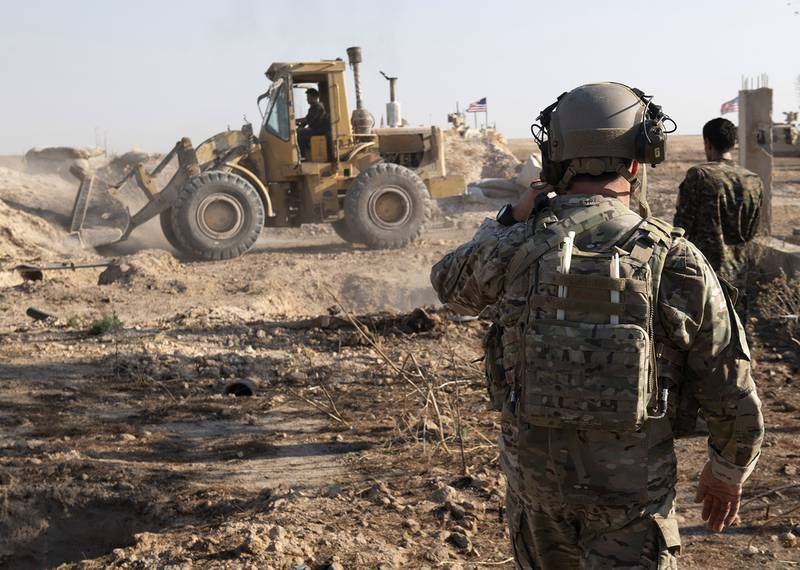 In this Aug. 22, 2019 photo, a U.S. service member watches as Syrian Democratic Forces remove military fortifications during the implementation of the security mechanism along the Turkey-Syria border in northeast Syria.