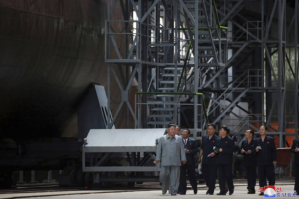 In this undated photo provided on Tuesday, July 23, 2019, North Korean leader Kim Jong Un, left, inspects a newly built submarine to be deployed soon, at an unknown location in North Korea.