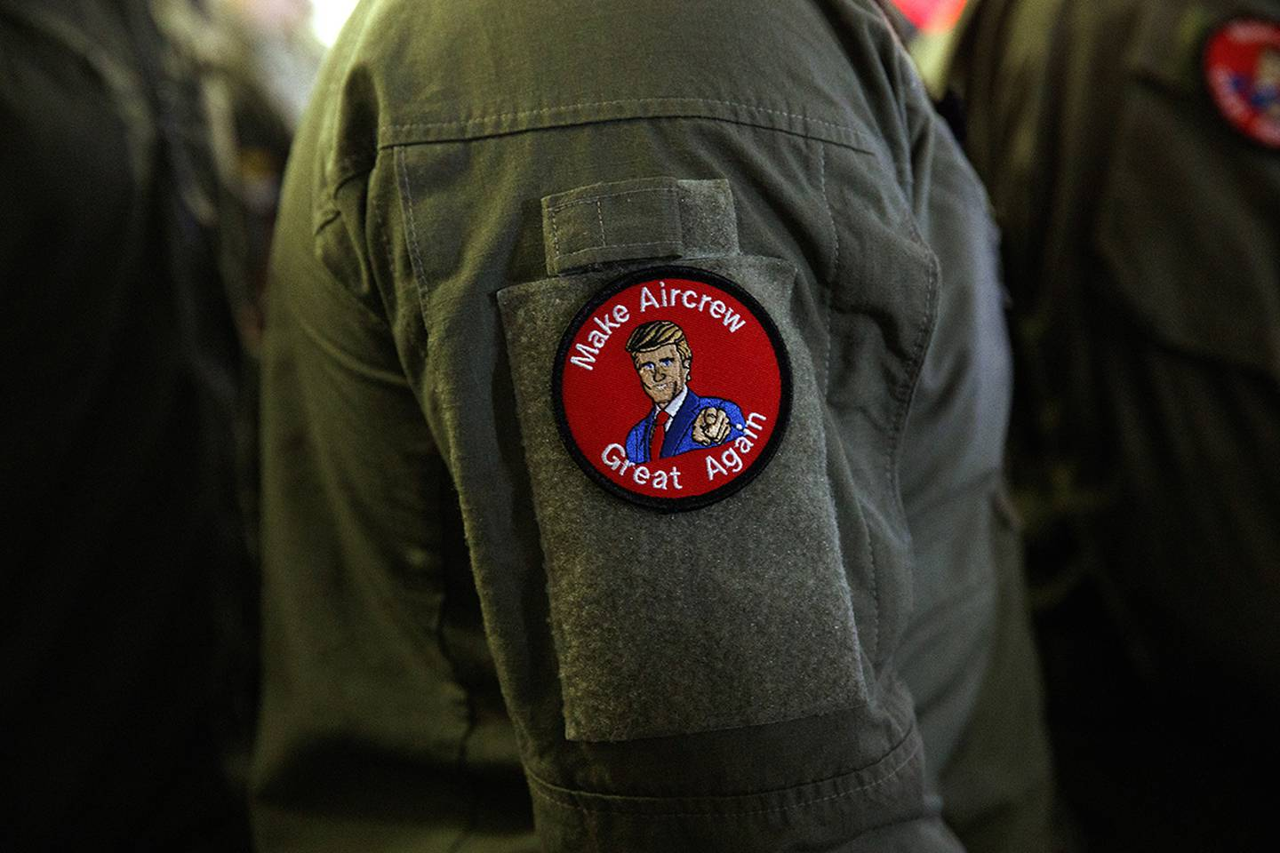 """A service member wears a patch that says """"Make Aircrew Great Again"""" as they listen to President Donald Trump speak to troops at a Memorial Day event aboard the USS Wasp on May 28, 2019, in Yokosuka, Japan."""
