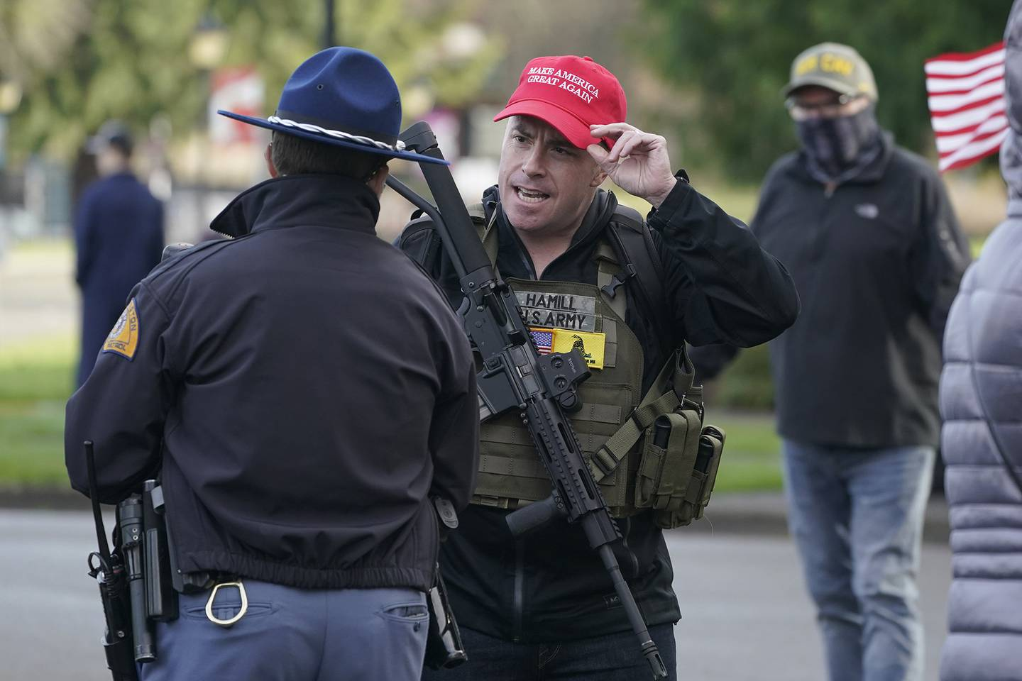 An armed supporter of President Donald Trump speaks casually with a Washington State Patrol trooper during a rally, Sunday, Jan. 10, 2021, at the Capitol in Olympia, Wash.