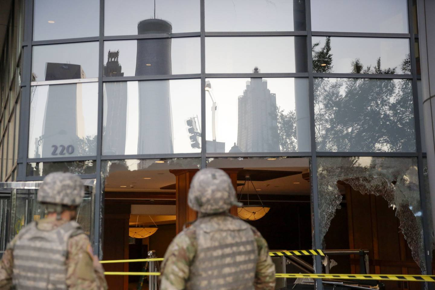 The National Guard looks at the damage done to downtown Atlanta in the aftermath of a demonstration against police violence on Saturday, May 30, 2020, in Atlanta.
