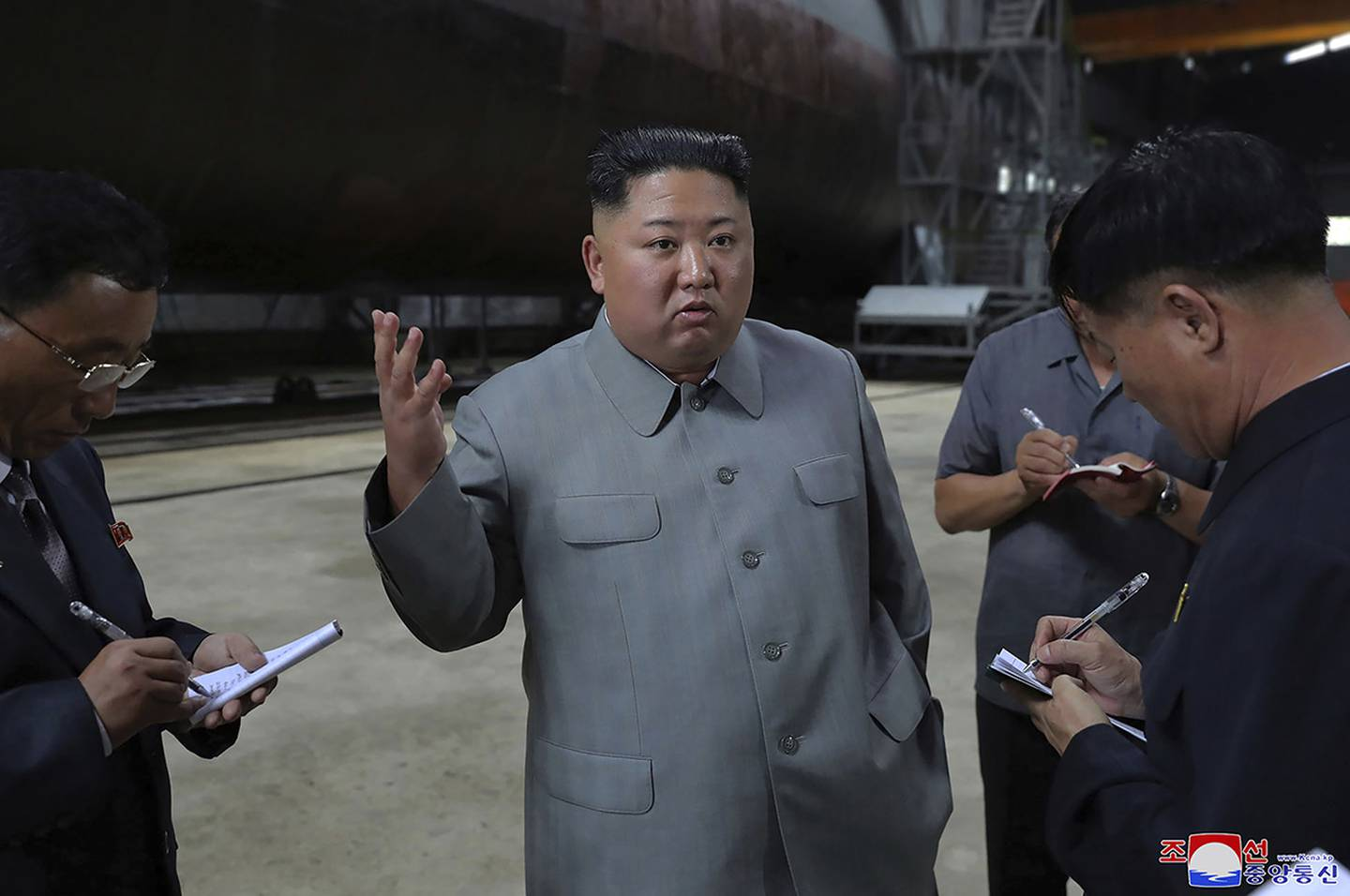 In this undated photo provided on Tuesday, July 23, 2019, North Korean leader Kim Jong Un, center, speaks while inspecting a newly built submarine to be deployed soon, at an unknown location in North Korea.