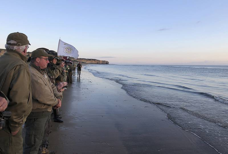 Re-enactors stand at the shore of Omaha Beach at sunrise as part of events to mark the 75th anniversary of D-Day on Omaha Beach in Vierville-sur-Mer, Normandy, France