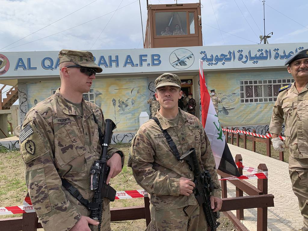 In this March 27, 2020, file photo, U.S. soldiers stand guard during the hand over ceremony of Qayyarah Airfield, Iraqi Security Forces, in the south of Mosul, Iraq.