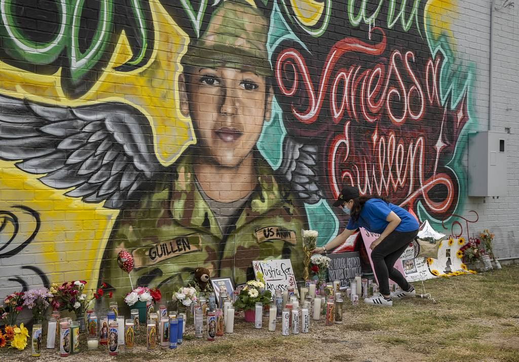 Mellisa Mendoza places white roses at a mural for Army Spc. Vanessa Guillen in Austin, Texas, on July 6, 2020.
