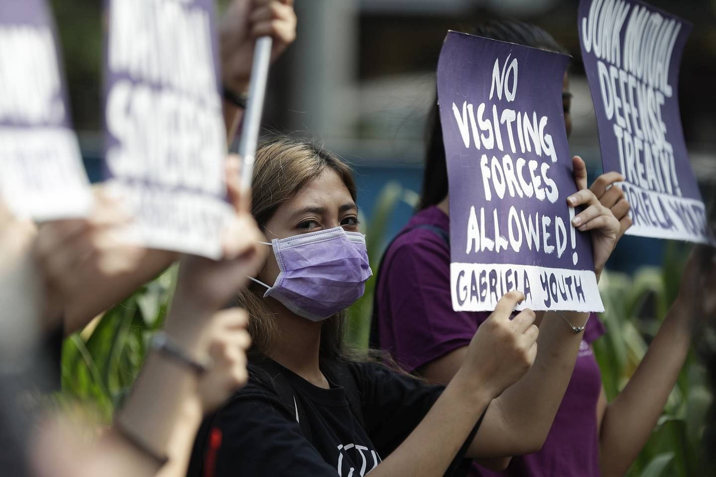 In this March 6, 2020, file photo, a woman protester wearing a protective mask holds a slogan during a rally outside the U.S. Embassy in Manila, Philippines, against the planned military exercises between the Philippines and U.S. under the Visiting Forces Agreement.