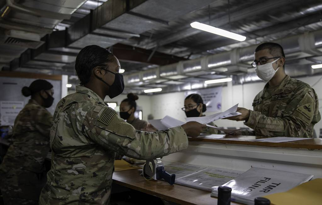 Army 2nd Lt. Daii Gardner and Spc. Natasha Washington hand out voting ballots to soldiers at the Theater Gateway, Camp Arifjan, Kuwait, Oct. 21, 2020.