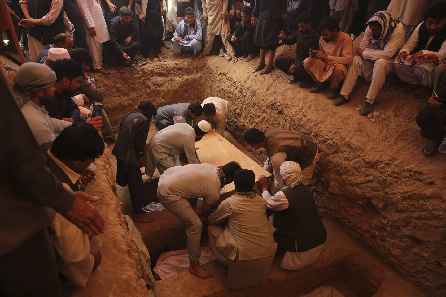 Afghans bury the bodies of victims of the Dubai City wedding hall bombing during a mass funeral in Kabul, Afghanistan, Sunday, Aug.18, 2019.