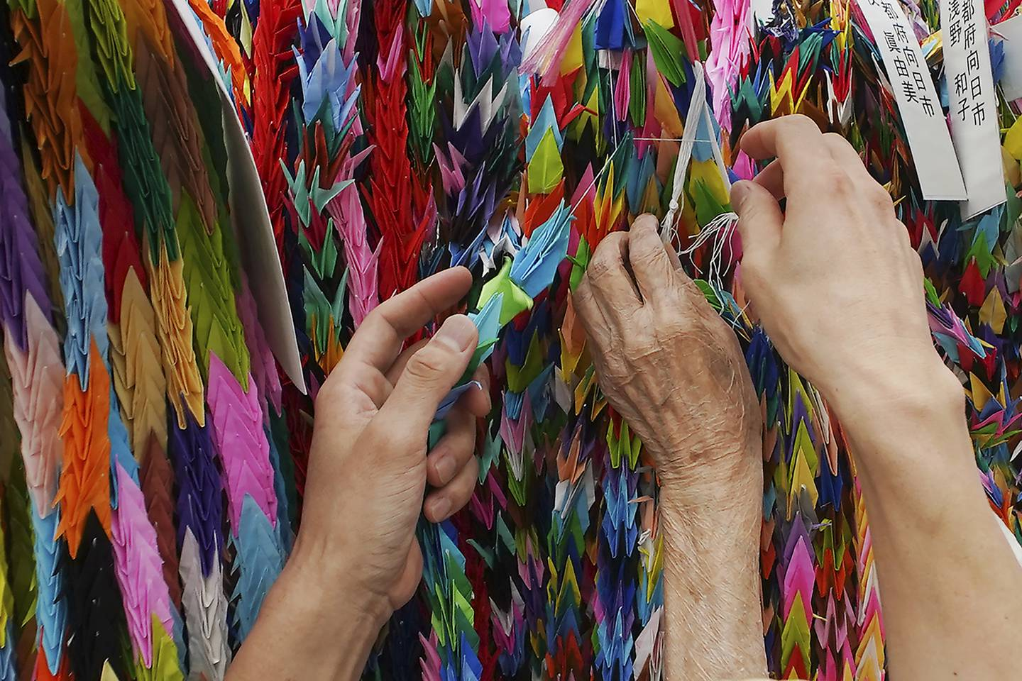 Hatsue Onda, center, is helped by Kengo Onda to offer strings of colorful paper cranes to the victims of the 1945 Atomic bombing near Hiroshima Peace Memorial Museum in Hiroshima, Japan, Monday, Aug. 3, 2020.