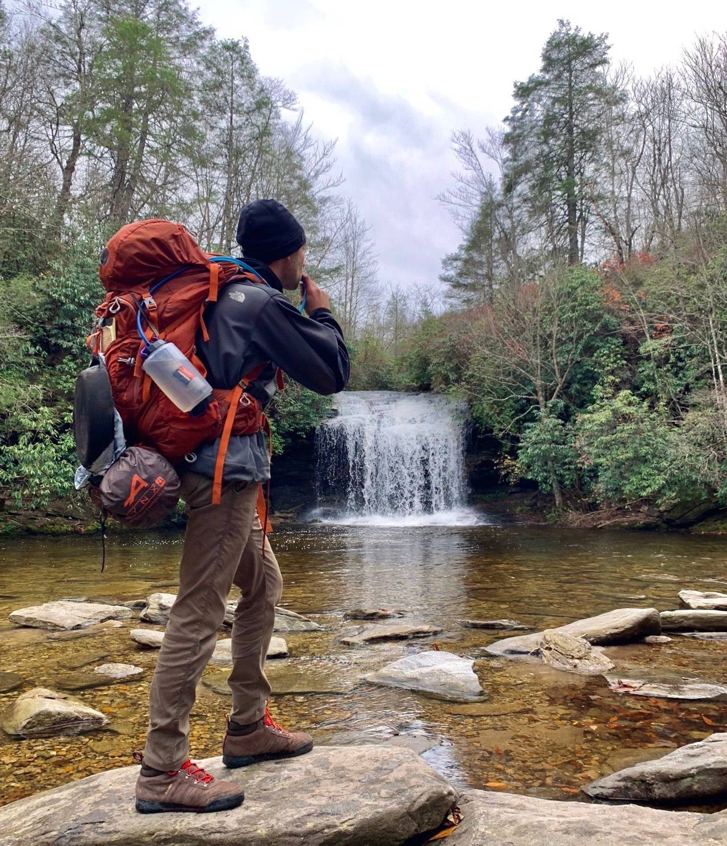 Hiker with backpack near waterfall