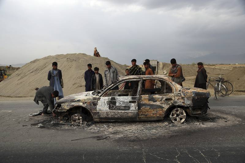 In this April 9, 2019, file photo, Afghans watch a civilian vehicle burnt after being shot by U.S. forces following an attack near the Bagram Air Base, north of Kabul, Afghanistan.