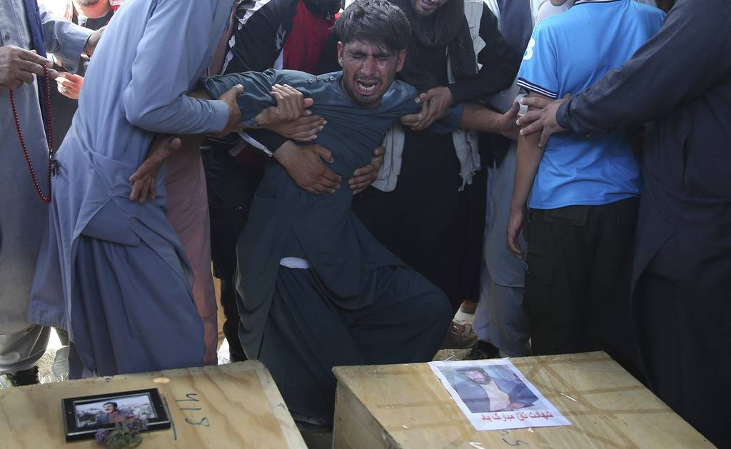 A relative wails near the coffins of victims of the Dubai City wedding hall bombing during a mass funeral in Kabul, Afghanistan, Sunday, Aug.18, 2019.