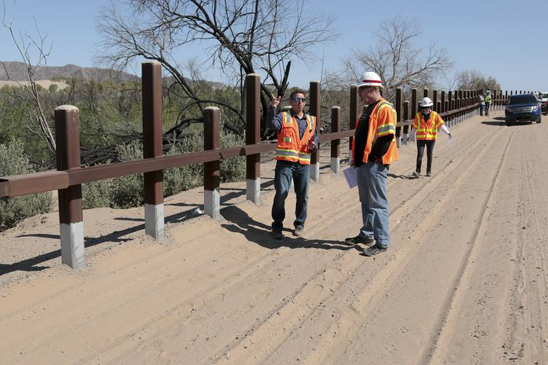A team from the U.S. Army Corps of Engineers and contractors discuss Customs and Border Protection pedestrian border wall fencing requirements outside Yuma, Ariz., on April 11, 2019.