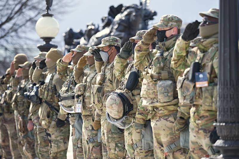 U.S. soldiers and airmen of the National Guard salute the presentation of the colors during the inauguration ceremony on Jan. 20, 2021, in Washington.