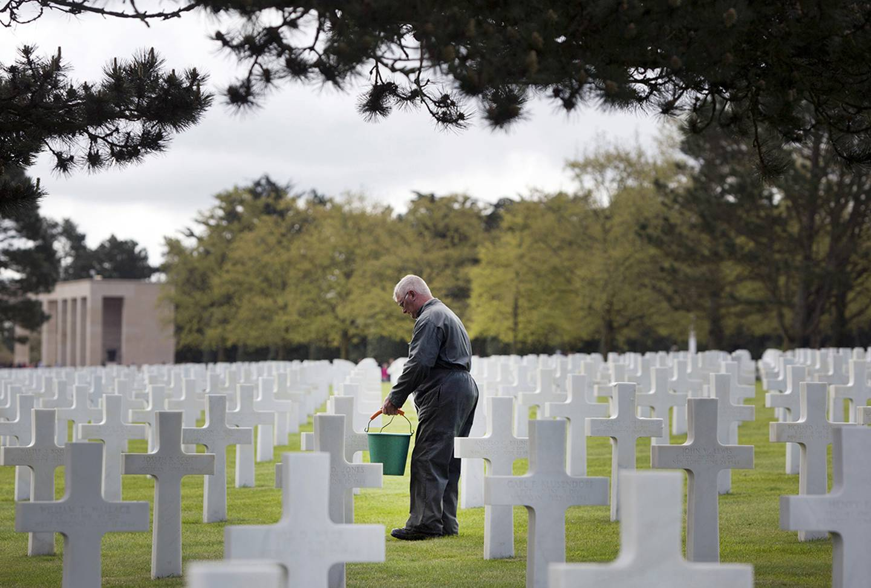 Normandy American Cemetery worker cleans headstones.