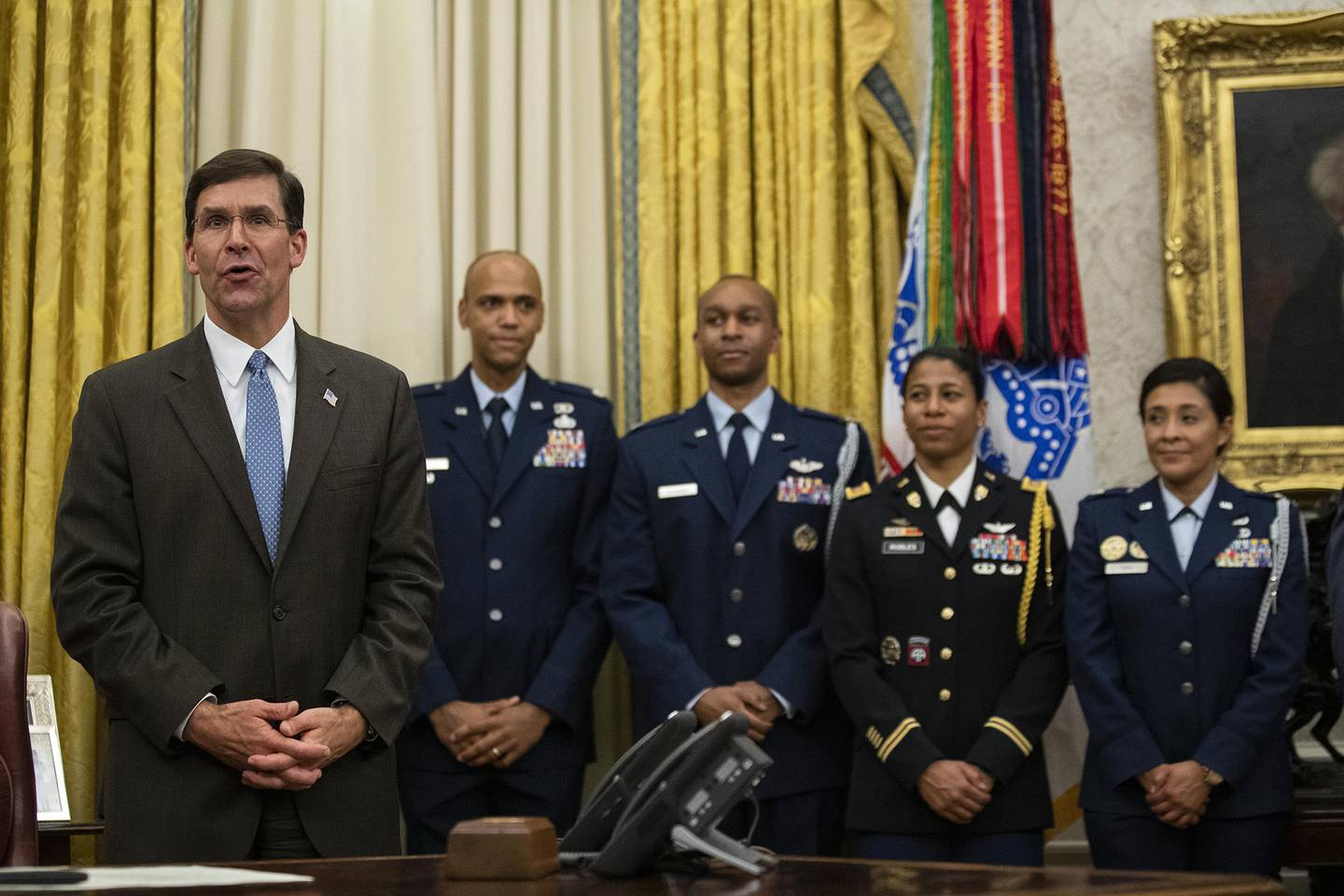 Secretary of Defense Mark Esper, left, speaks after a ceremony to swear in Gen. Charles Q. Brown Jr. as chief of staff of the Air Force in the Oval Office of the White House, Tuesday, Aug. 4, 2020, in Washington.