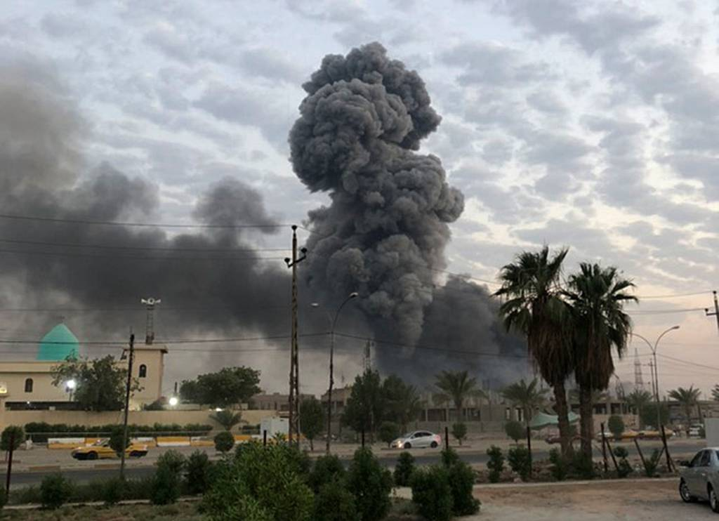 In this Monday, Aug. 12, 2019, photo, plumes of smoke rise after an explosion at a military base southwest of Baghdad, Iraq.